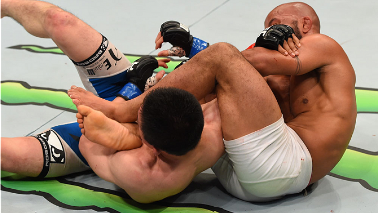 MONTREAL, QC - APRIL 25:   (R-L) Demetrious Johnson of the United States secures an arm bar submission against Kyoji Horiguchi in their UFC flyweight championship bout during the UFC 186 event at the Bell Centre on April 25, 2015 in Montreal, Quebec, Cana