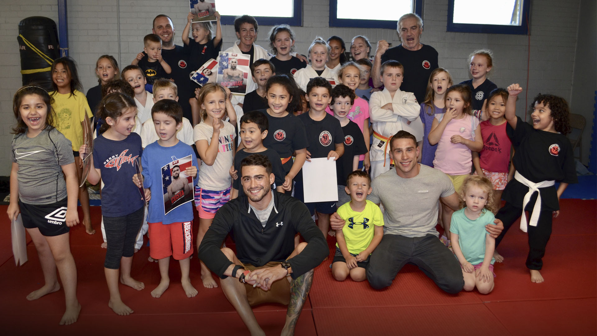 Boston-based fighters Randy Costa and Kyle Bochniak poss with young fans at Ultimate Self Defense