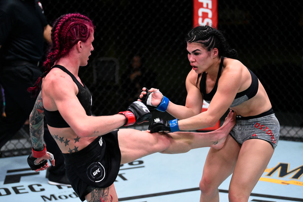 LAS VEGAS, NEVADA - NOVEMBER 28: (L-R) Gina Mazany kicks the body of Rachael Ostovich in their women's flyweight bout during the UFC Fight Night