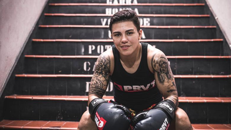 Jéssica Andrade de luvas sentada na escada da academia PRVT.