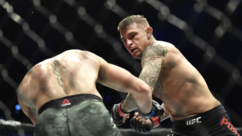 Dustin Poirier punches Conor McGregor of Ireland in a lightweight fight during the UFC 257 event inside Etihad Arena on UFC Fight Island on January 23 2021 in Abu Dhabi United Arab Emirates (Photo by Chris Unger/Zuffa LLC)