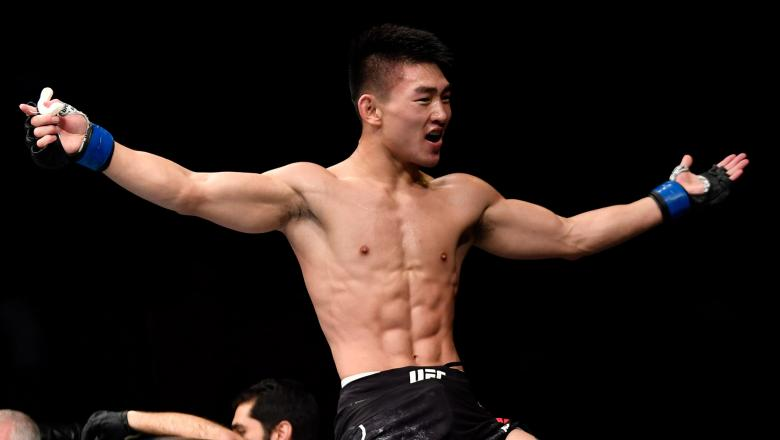 Song Yadong of China celebrates after his knockout victory over Felipe Arantes of Brazil in their bantamweight bout during the UFC Fight Night event at the Singapore Indoor Stadium on June 23 2018 in Singapore (Photo by Jeff Bottari/Zuffa LLC)