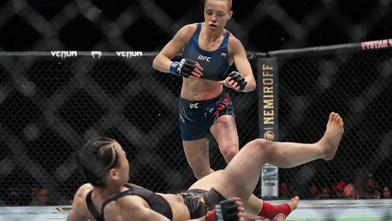 Rose Namajunas of the United States pounces on Zhang Weili of China during the Women's Strawweight Title bout of UFC 261 at VyStar Veterans Memorial Arena on April 24 2021 in Jacksonville FL (Photo by Alex Menendez/Getty Images)