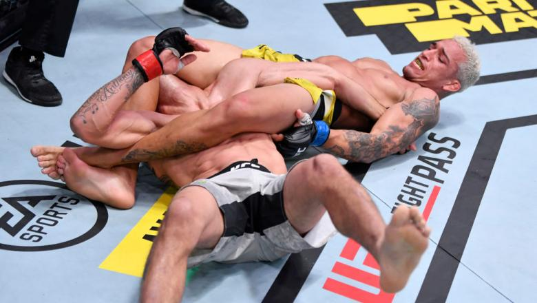 LAS VEGAS, NEVADA - DECEMBER 12: (R-L) Charles Oliveira of Brazil attempts to submit Tony Ferguson in their lightweight bout during the UFC 256 e