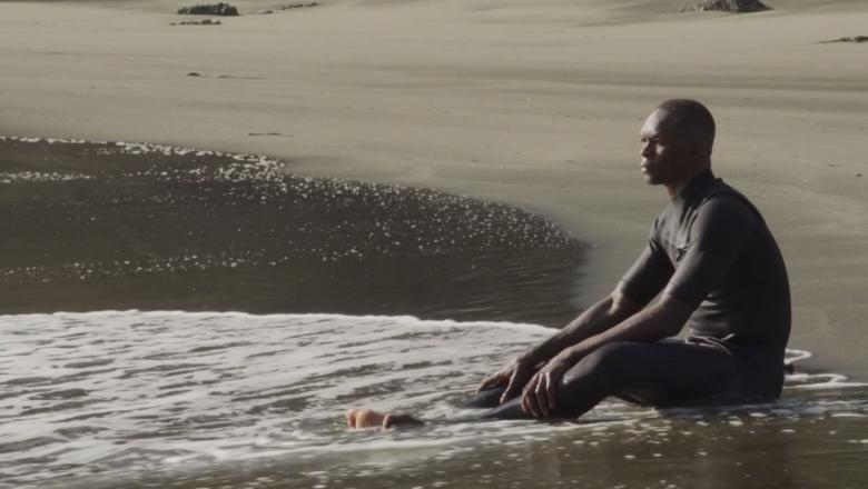 Israel Adesanya sits on the beach in between training. Watch UFC 263 Countdown Now