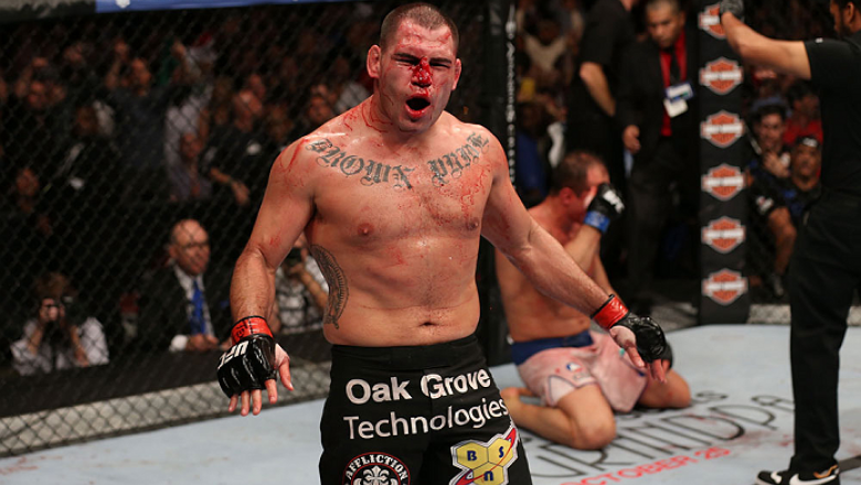 HOUSTON, TEXAS - OCTOBER 19:  Cain Velasquez (black shorts) celebrates after defeating Junior Dos Santos by TKO after referee Herb Dean calls a stop to the fight in their UFC heavyweight championship bout at the Toyota Center on October 19, 2013 in Housto