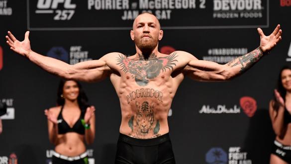 Conor McGregor posa com os braços erguidos na pesagem do UFC 257