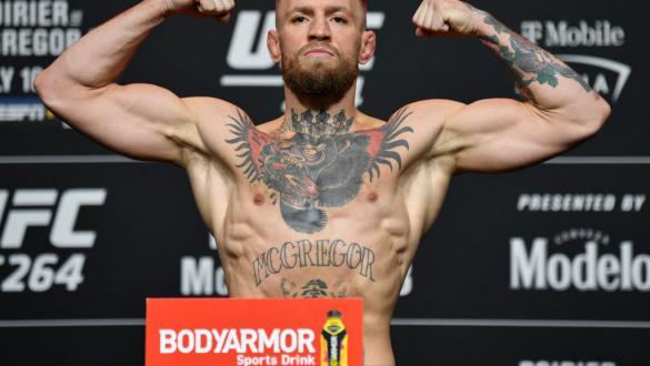 Conor McGregor posa com os braços flexionados na pesagem do UFC 264.