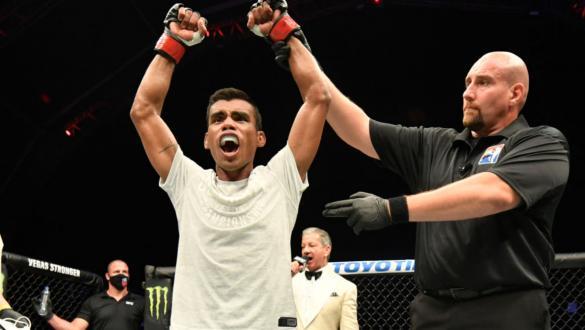 Raulian Paiva tem o braço erguido ao ser declarado vencedor da luta com Zhalgas Zhumagulov