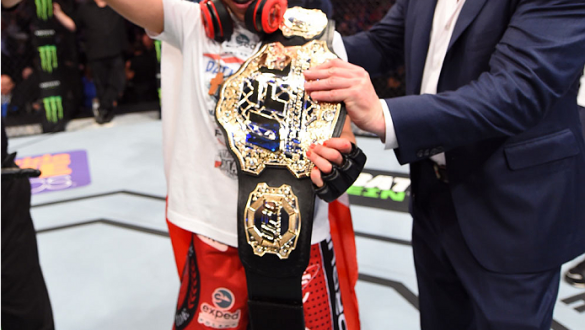 DALLAS, TX - MARCH 14:  (R-L) UFC President Dana White gives Joanna Jedrzejczyk the UFC women's strawweight championship belt after defeating Carla Esparza by TKO during the UFC 185 event at the American Airlines Center on March 14, 2015 in Dallas, Texas.