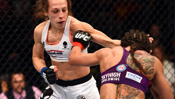 PHOENIX, AZ - DECEMBER 13:  (R-L) Claudia Gadelha of Brazil punches Joanna Jedrzejczyk of Poland in their women's strawweight fight during the UFC Fight Night event at the U.S. Airways Center on December 13, 2014 in Phoenix, Arizona.  (Photo by Josh Hedge
