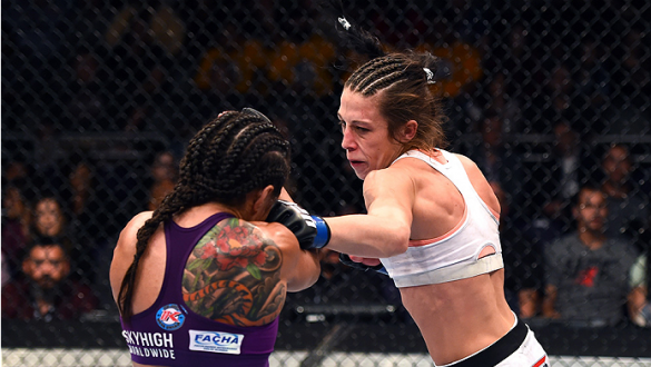 PHOENIX, AZ - DECEMBER 13:  (R-L) Joanna Jedrzejczyk of Poland punches Claudia Gadelha of Brazil in their women's strawweight fight during the UFC Fight Night event at the U.S. Airways Center on December 13, 2014 in Phoenix, Arizona.  (Photo by Josh Hedge