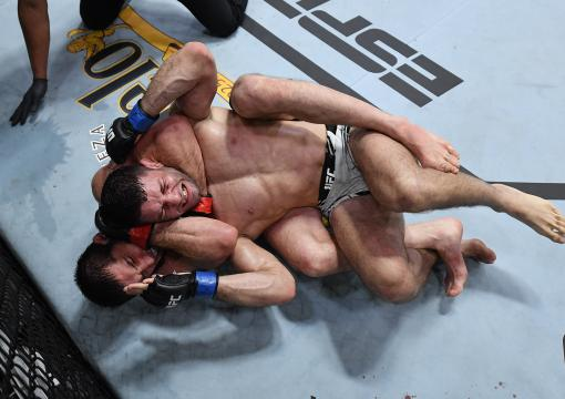 Islam Makhachev of Russia secures a rear choke submission against Thiago Moises of Brazil in their lightweight bout during the UFC Fight Night event at UFC APEX on July 17, 2021 in Las Vegas, Nevada. (Photo by Jeff Bottari/Zuffa LLC)
