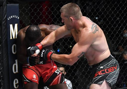 Dustin Jacoby punches Darren Stewart of England in a middleweight fight during the UFC Fight Night event at UFC APEX on August 28 2021 in Las Vegas Nevada. (Photo by Chris Unger/Zuffa LLC)