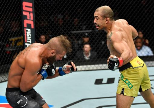 Jose Aldo of Brazil drops Jeremy Stephens with a punch to the body in their featherweight bout during the UFC Fight Night event at Scotiabank Saddledome on July 28 2018 in Calgary Alberta Canada (Photo by Jeff Bottari/Zuffa LLC/Zuffa LLC via Getty Images)