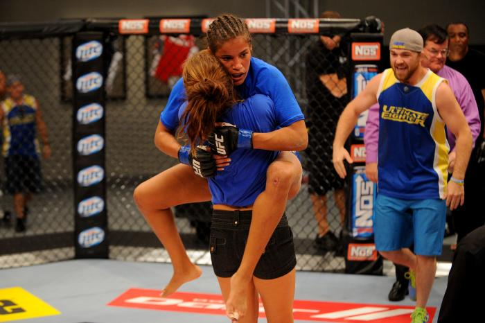 LAS VEGAS, NV - JUNE 6:  Coach Miesha Tate celebrates with Julianna Pena (blue shorts) after she submits Shayna Baszler (not pictured) in their preliminary fight during filming of season eighteen of The Ultimate Fighter on June 6, 2013 in Las Vegas, Nevada. (Photo by Al Powers/Zuffa LLC via Getty Images)