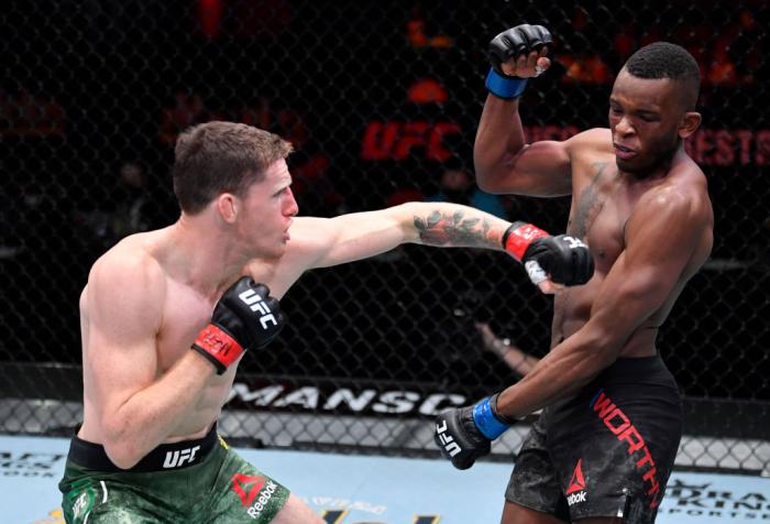 Jamie Mullarkey of Australia punches Khama Worthy in their lightweight fight during the UFC 260 event at UFC APEX on March 27, 2021 in Las Vegas, Nevada. (Photo by Jeff Bottari/Zuffa LLC)