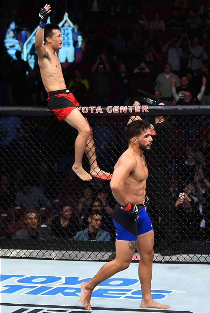 HOUSTON, TX - FEBRUARY 04:  (L-R) Chan Sung Jung of South Korea celebrates his victory over Dennis Bermudez in their featherweight bout during the UFC Fight Night event at the Toyota Center on February 4, 2017 in Houston, Texas. (Photo by Jeff Bottari/Zuf