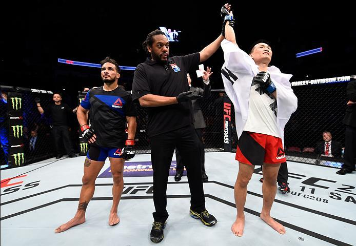 HOUSTON, TX - FEBRUARY 04:  (R-L) Chan Sung Jung of South Korea celebrates his victory over Dennis Bermudez in their featherweight bout during the UFC Fight Night event at the Toyota Center on February 4, 2017 in Houston, Texas. (Photo by Jeff Bottari/Zuf