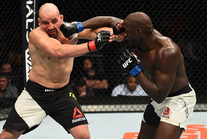 BROOKLYN, NEW YORK - FEBRUARY 11:  (R-L) Jared Cannonier kicks Glover Teixeira of Brazil in their light heavyweight bout during the UFC 208 event inside Barclays Center on February 11, 2017 in Brooklyn, New York. (Photo by Jeff Bottari/Zuffa LLC/Zuffa LLC