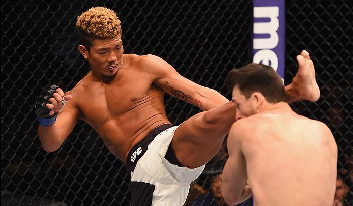 LAS VEGAS, NV - MARCH 05: (L-R) Teruto Ishihara of Japan kicks Julian Erosa in their featherweight bout during the UFC 196 event inside MGM Grand Garden Arena on March 5, 2016 in Las Vegas, Nevada.  (Photo by Josh Hedges/Zuffa LLC/Zuffa LLC via Getty Imag