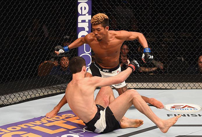LAS VEGAS, NV - MARCH 05:  Teruto Ishihara of Japan (top) punches Julian Erosa in their featherweight bout during the UFC 196 event inside MGM Grand Garden Arena on March 5, 2016 in Las Vegas, Nevada.  (Photo by Josh Hedges/Zuffa LLC/Zuffa LLC via Getty I