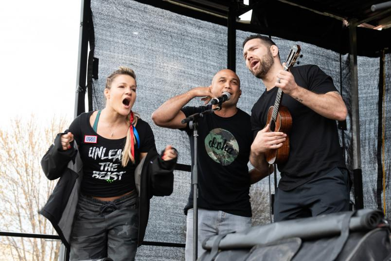 UFC athletes Felice Herrig, BJ Penn and Chris Weidman sing during a leg of the USO Tour overseas (DoD Photo by U.S. Army Sgt. James K. McCann).