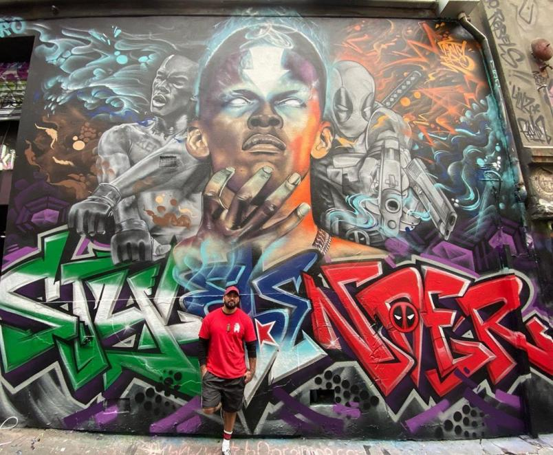 The Artist Poses In Front Of His Adesanya Mural. From His Instagram @mattybro_art