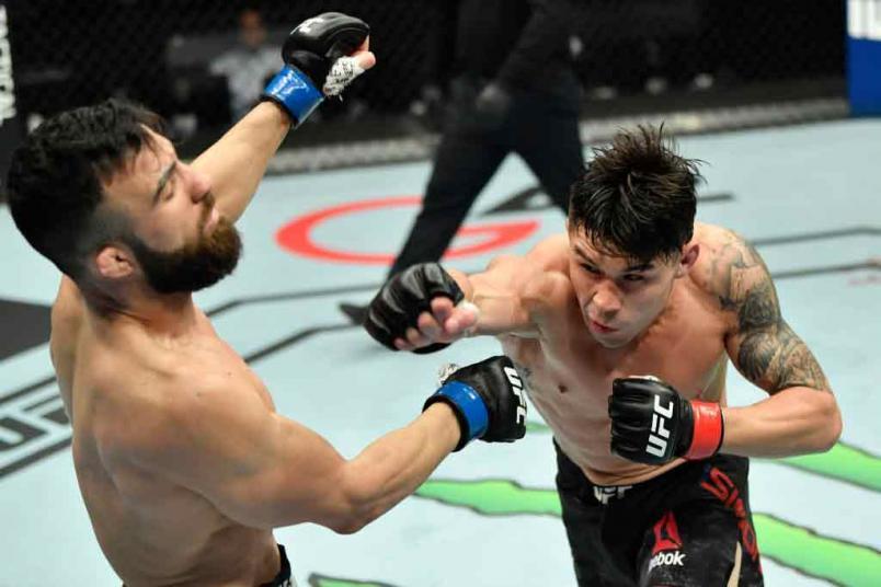 Ricky Simon punches Gaetano Pirrello of Belgium in a bantamweight fight during the UFC Fight Night event at Etihad Arena on UFC Fight Island on January 20, 2021 in Abu Dhabi, United Arab Emirates. (Photo by Jeff Bottari/Zuffa LLC)