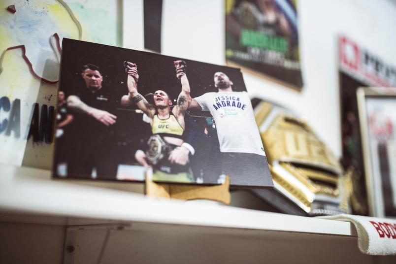 Porta retrato com a foto de Jéssica Andrade recebendo o cinturão do UFC ao lado do treinador Gilliard Paraná.