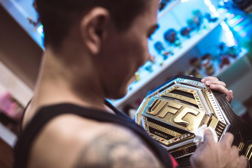 Jéssica Andrade olha para o cinturão do UFC.