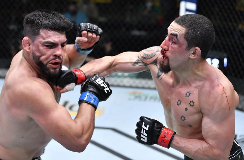 Robert Whittaker of Australia punches Kelvin Gastelum in a middleweight fight during the UFC Fight Night event at UFC APEX on April 17, 2021 in Las Vegas, Nevada. (Photo by Chris Unger/Zuffa LLC)
