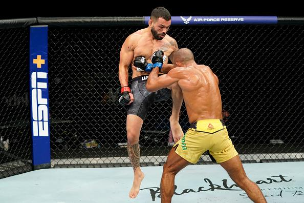 Dan Ige knees Edson Barboza of Brazil in their featherweight fight during the UFC Fight Night event at VyStar Veterans Memorial Arena on May 16, 2020 in Jacksonville, Florida. (Photo by Cooper Neill/Zuffa LLC)