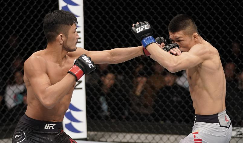 Kyung Ho Kang of South Korea punches Liu Pingyuan of China in their bantamweight fight during the UFC Fight Night event at Sajik Arena 3 on December 21 2019 in Busan South Korea. (Photo by Jeff Bottari/Zuffa LLC)