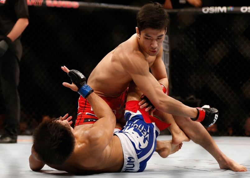 Kang Kyung Ho punches Shunichi Shimizu in their bantamweight bout during the UFC Fight Night event at the Marina Bay Sands Resort on January 4 2014 in Singapore. (Photo by Josh Hedges/Zuffa LLC)