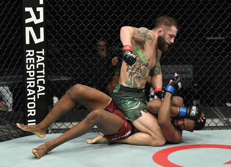 Michael Chiesa punches Neil Magny in a welterweight fight during the UFC Fight Night event at Etihad Arena on UFC Fight Island on January 20 2021 in Abu Dhabi United Arab Emirates. (Photo by Jeff Bottari/Zuffa LLC)