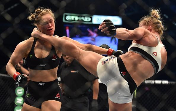 Holly Holm of the US (R) lands a kick to the neck to knock out compatriot Ronda Rousey and win the UFC title fight in Melbourne on November 15, 2015.   RESTRICTED TO EDITORIAL USE NO ADVERTISING USE NO PROMOTIONAL USE NO MERCHANDISING USE.  AFP PHOTO/Paul