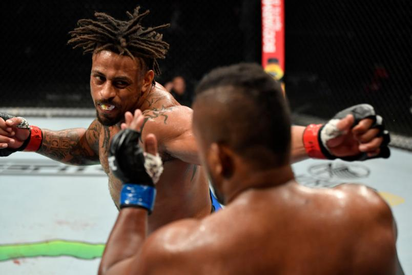 JACKSONVILLE, FLORIDA - MAY 09: (L-R) Greg Hardy punches Yorgan De Castro in their heavyweight fight during the UFC 249
