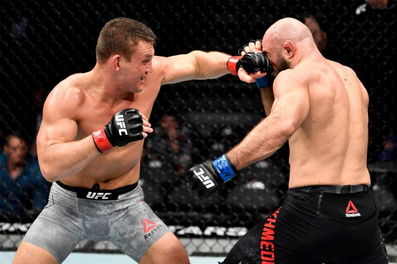 LAS VEGAS, NEVADA - DECEMBER 14: (L-R) Ian Heinisch punches Omari Akhmedov of Russia in their middleweight bout during the UFC
