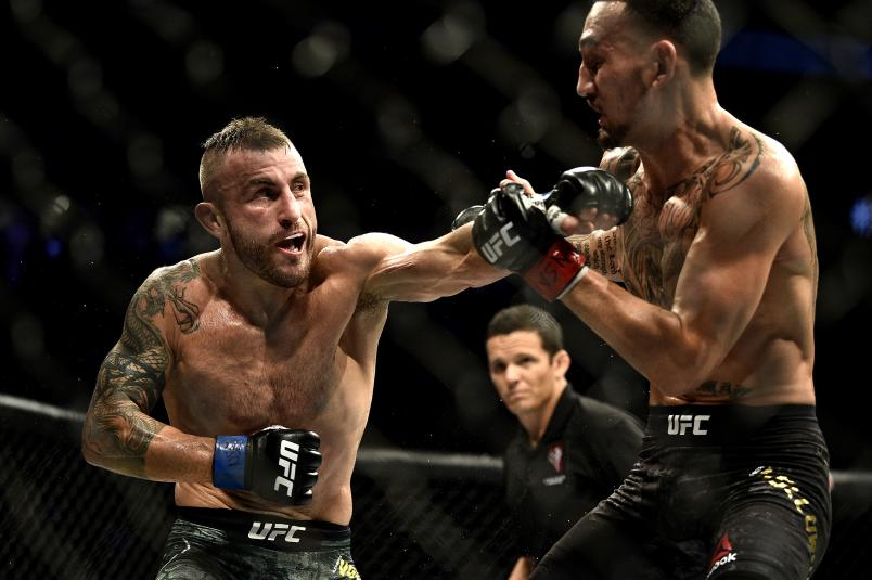 LAS VEGAS, NEVADA - DECEMBER 14: (L-R) Alexander Volkanovski of Australia punches Max Holloway in their UFC featherweight championship bout during the UFC 245