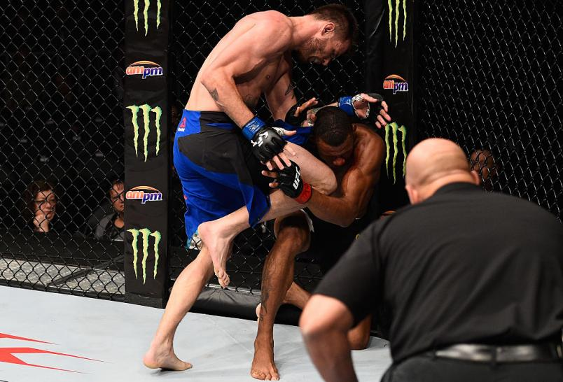 LAS VEGAS, NV - DECEMBER 30: Tim Means (blue trunks) knees Alex Oliveira of Brazil in their welterweight bout during the UFC 207 event at T-Mobile Arena on December 30, 2016 in Las Vegas, Nevada.  (Photo by Jeff Bottari/Zuffa LLC/Zuffa LLC via Getty Image