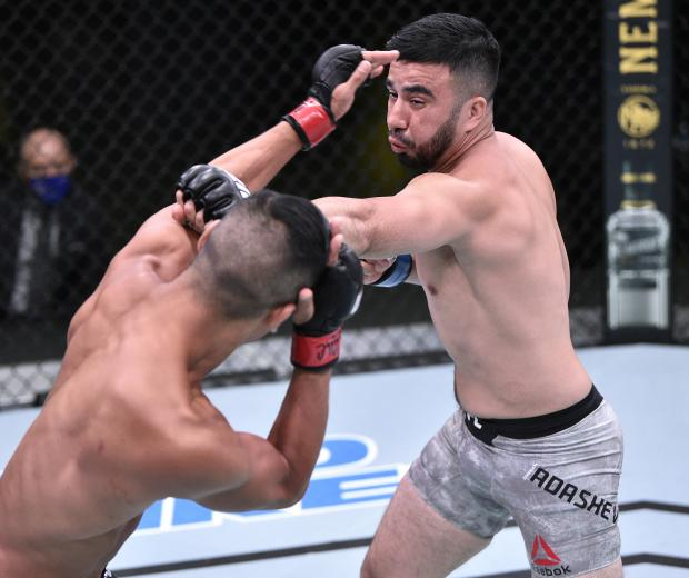 Zarrukh Adashev of Uzbekistan punches Tyson Nam in their bantamweight fight during the UFC Fight Night event at UFC APEX on June 13, 2020 in Las Vegas, Nevada. (Photo by Chris Unger/Zuffa LLC)