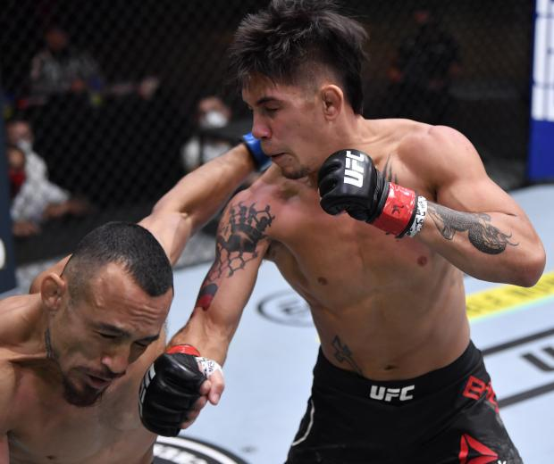TJ Brown punches Danny Chavez in their featherweight bout during the UFC 252 event at UFC APEX on August 15, 2020 in Las Vegas, Nevada. (Photo by Jeff Bottari/Zuffa LLC)