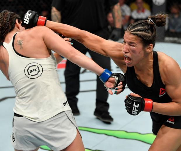 Julianna Pena punches Nico Montano in their women's bantamweight bout during the UFC Fight Night event at Golden 1 Center on July 13, 2019 in Sacramento, California. (Photo by Jeff Bottari/Zuffa LLC)