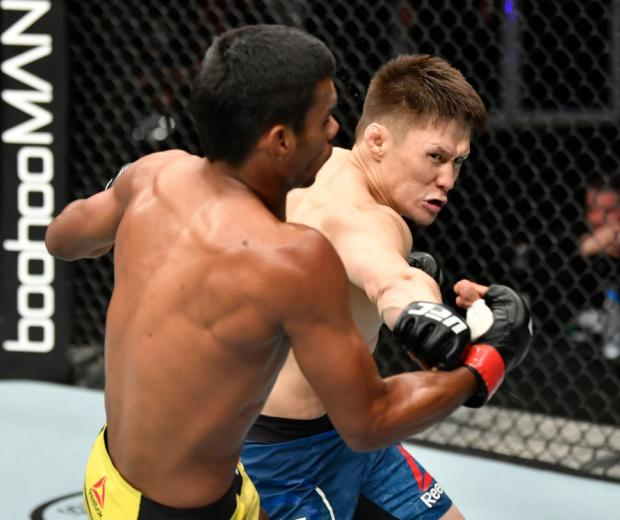Zhalgas Zhumagulov of Kazakhstan punches Raulian Paiva of Brazil in their flyweight fight during the UFC 251 event at Flash Forum on UFC Fight Island on July 12, 2020 on Yas Island, Abu Dhabi, United Arab Emirates. (Photo by Jeff Bottari/Zuffa LLC via Getty Images)