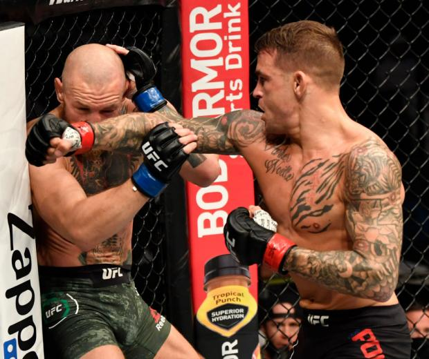 Dustin Poirier punches Conor McGregor of Ireland in a lightweight fight during the UFC 257 event inside Etihad Arena on UFC Fight Island on January 23, 2021 in Abu Dhabi, United Arab Emirates. (Photo by Jeff Bottari/Zuffa LLC)