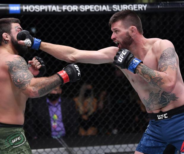 Tim Means punches Mike Perry in their welterweight bout during the UFC 255 event at UFC APEX on November 21, 2020 in Las Vegas, Nevada. (Photo by Jeff Bottari/Zuffa LLC)