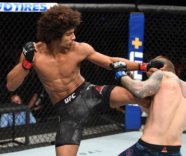 Alex Caceres kicks Steven Peterson in their featherweight bout during the UFC Fight Night