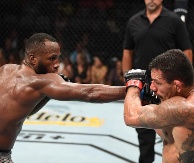 Leon Edwards of Jamaica punches Rafael Dos Anjos of Brazil in their welterweight bout during the UFC Fight Night