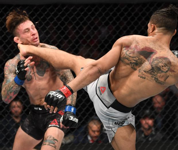 Kevin Lee kicks Gregor Gillespie in their lightweight bout during the UFC 244